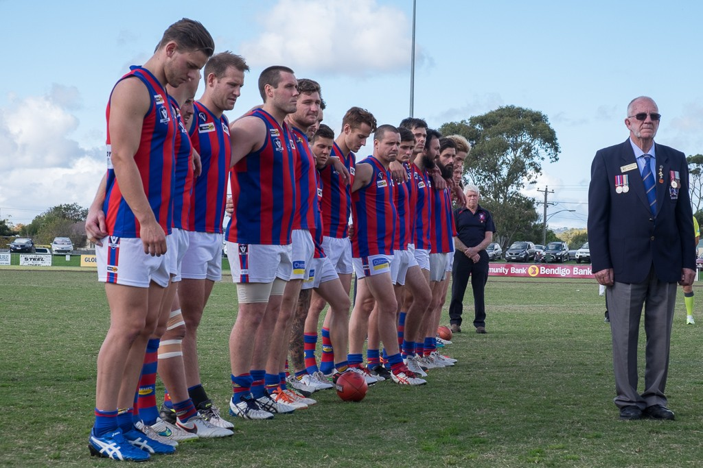 Players from both Dromana v Rye Football Clubs stand in a minute's silence as part of the pre-game ANZAC Commemoration Ceremony. Dromana Recreation Reserve. 23 April 2016.